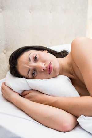 desolaci�n: Pretty brunette trying to sleep on bed at home