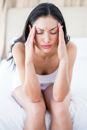 perplexed: Pretty brunette perplexed on bed at home Stock Photo