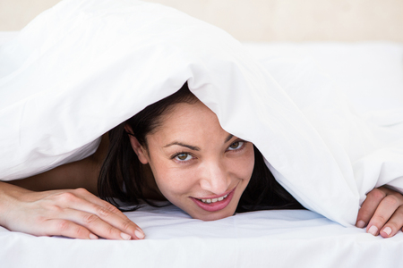 inquiring: Pretty brunette looking at camera and hiding under the duvet at home