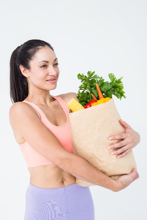 woman holding bag: Slim woman holding bag with healthy food on white background Stock Photo