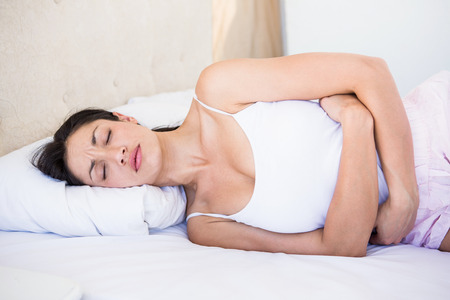 stomach pain: Pretty brunette with stomach pain on bed