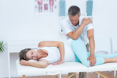 woman back pain: Doctor massaging his patient hip in medical office Stock Photo