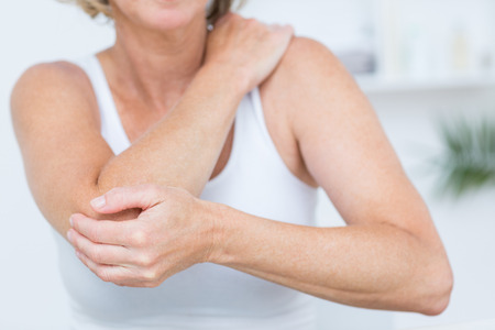 epaule douleur: Femme ayant douleur au coude en cabinet m�dical