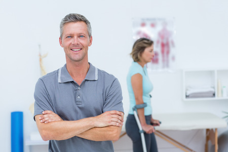 naprapathy: Doctor smiling at camera while his patient standing with crutch in medical office Stock Photo