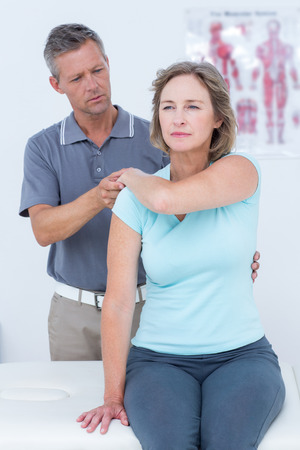 strength therapy: Woman stretching her arm with her doctor in medical office