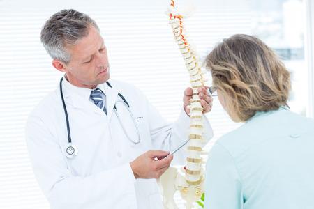 espina dorsal: Doctor que señala la columna vertebral anatómica en el consultorio médico