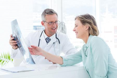 doctores: Doctor que tiene conversaci�n con su paciente y la celebraci�n de rayos x en el consultorio m�dico Foto de archivo
