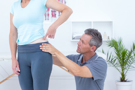 Physiotherapist examining his patient back in medical office photo