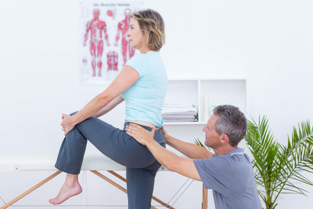 naprapathy: Physiotherapist examining his patient back in medical office Stock Photo