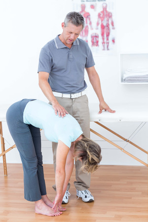 postural integration: Physiotherapist examining his patient back in medical office Stock Photo