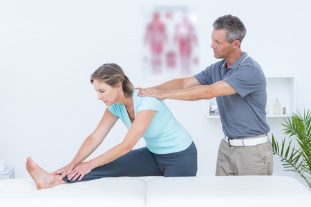 bend over: Physiotherapist helping his patient stretching in medical office Stock Photo