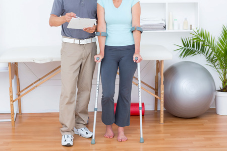 muscle retraining: Woman using crutch and talking with her doctor in medical office