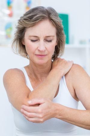 dolor muscular: Mujer que tiene dolor en el codo en el consultorio médico Foto de archivo