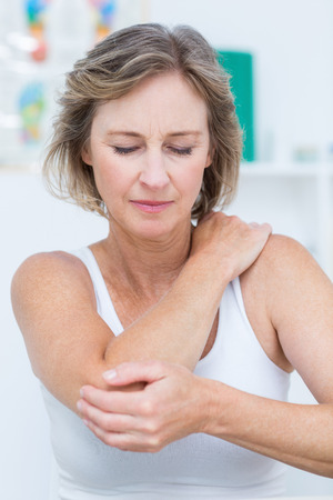 aching muscles: Woman having elbow pain in medical office Stock Photo