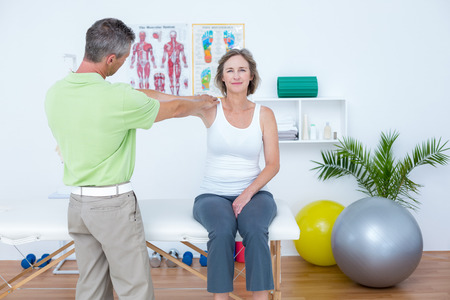 alternative wellness: Doctor stretching his patients arm in medical office Stock Photo