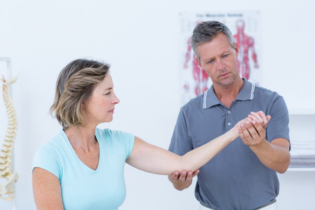 pain: Doctor stretching his patients arm in medical office Stock Photo