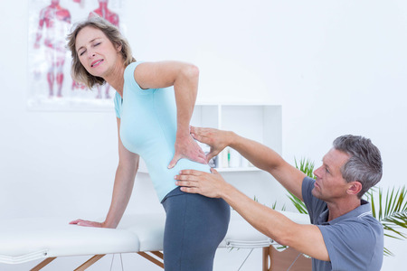 Physiotherapist examining his patient back in medical office Reklamní fotografie