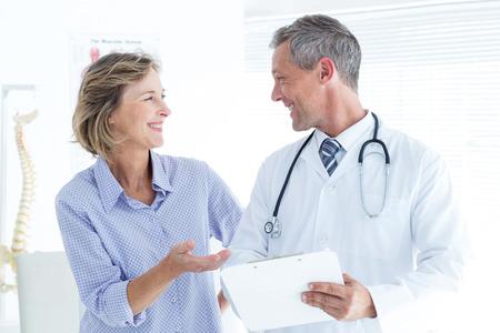 medico con paciente: Doctor que muestra sus notas a su paciente en el consultorio médico