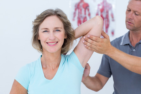 fisioterapia: Mujer que estira sus brazos con su m�dico en el consultorio m�dico Foto de archivo
