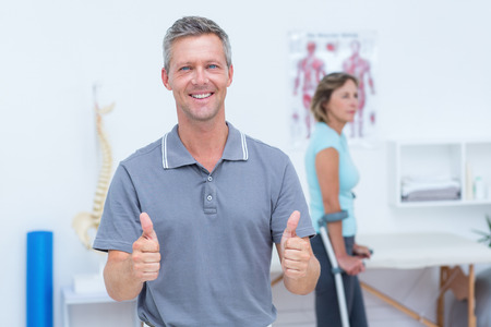 retraining: Doctor smiling at camera while his patient standing with crutch in medical office Stock Photo