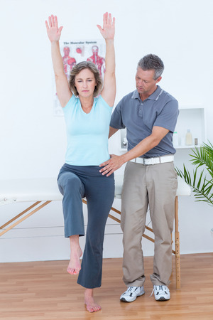 muscle retraining: Physiotherapist examining his patient back in medical office Stock Photo