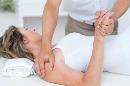 fisioterapia: Doctor en flexi�n del brazo del paciente en el consultorio m�dico