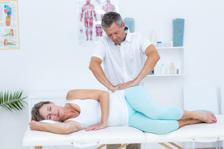 hip: Doctor massaging his patient hip in medical office Stock Photo