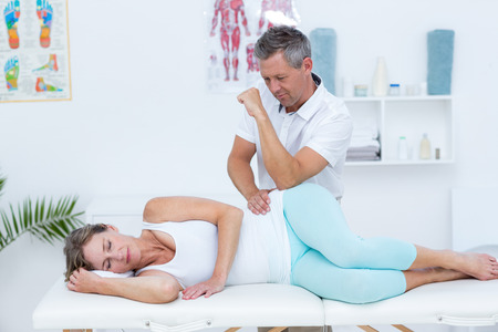 muscle pain: Doctor massaging his patient hip in medical office Stock Photo