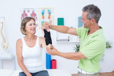 fisioterapia: Doctor que examina a sus pacientes la mu�eca en el consultorio m�dico