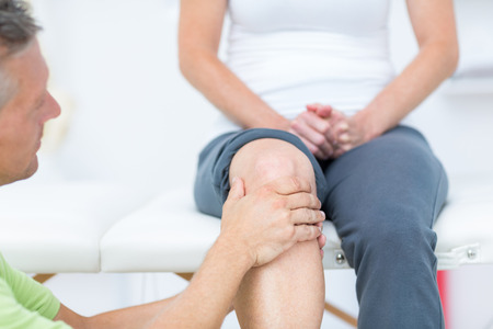 Doctor examining his patients knee in medical office Stock Photo