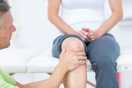 paciente: Doctor que examina a sus pacientes de la rodilla en el consultorio médico