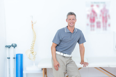 naprapathy: Doctor smiling at camera in medical office Stock Photo