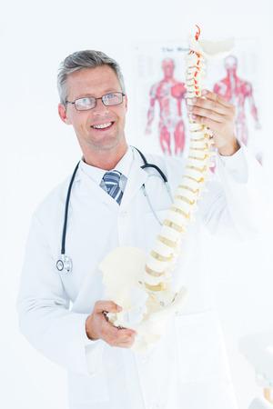 columna vertebral: Doctor que sostiene la columna vertebral anat�mica y sonriendo a la c�mara en el consultorio m�dico