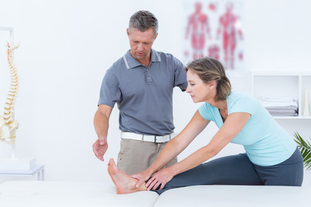 posture correction: Physiotherapist helping his patient stretching in medical office Stock Photo