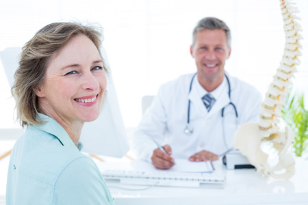 Patient and doctor smiling at camera in medical office Stockfoto