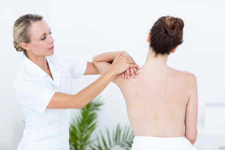physiotherapist: Physiotherapist doing shoulder massage in medical office
