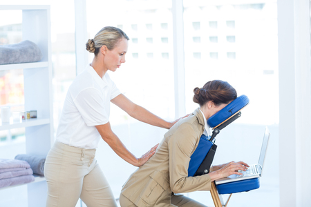massage chair: Businesswoman having back massage while using her laptop in medical office Stock Photo