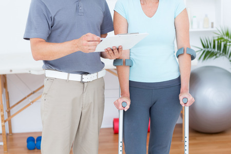 naprapathy: Woman using crutch and talking with her doctor in medical office