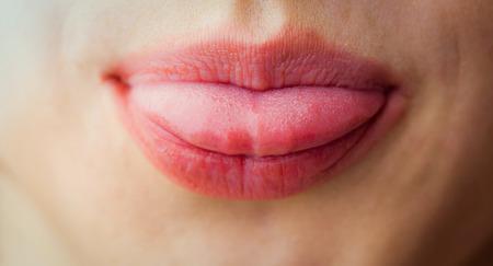 sacar la lengua: Mujer sacando la lengua en primer plano