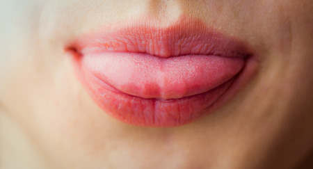Woman sticking her tongue out in close up Stock Photo
