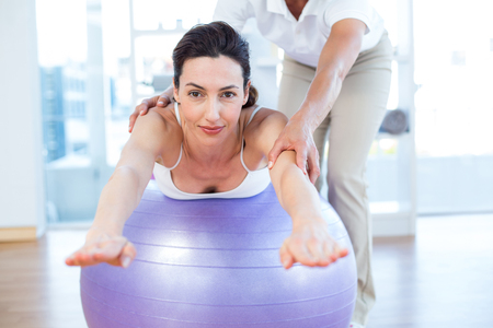 Trainer helping woman on exercise ball in medical office Stock Photo