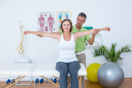 physical pressure: Doctor stretching his patients arms in medical office