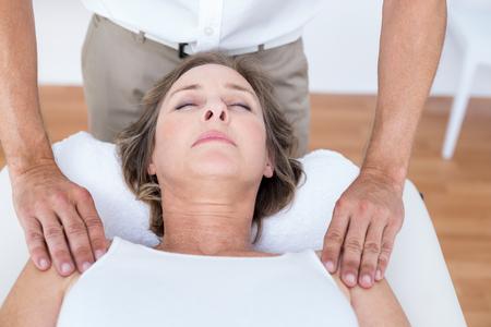 fisioterapia: Mujer que recibe masaje del hombro en el consultorio médico Foto de archivo
