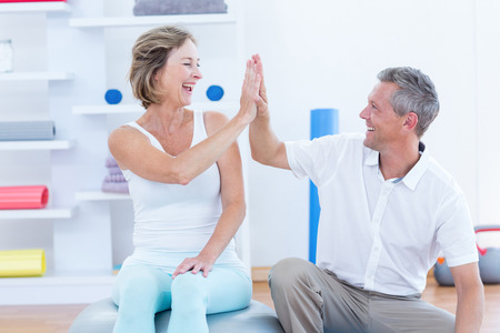 doctor patient: Doctor and patient smiling at each other in medical office