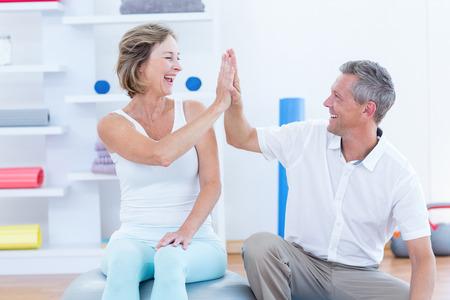 medico con paciente: Médico y el paciente sonriendo el uno al otro en el consultorio médico