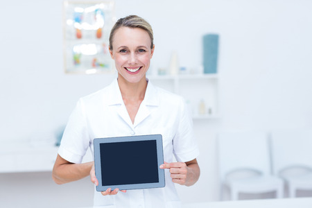 Smiling doctor looking at camera and showing tablet in medical office Reklamní fotografie
