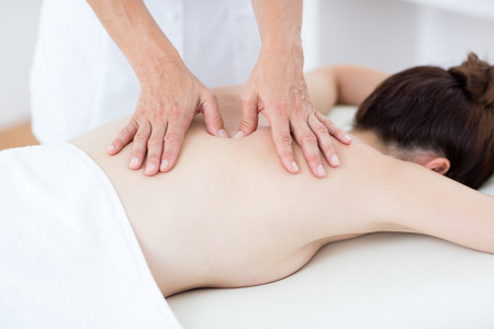 physiotherapist: Physiotherapist doing back massage in medical office Stock Photo
