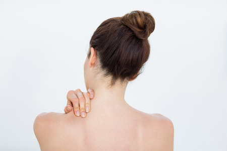 hombros: Woman touching her shoulder in medical office