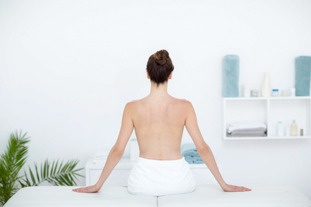 mid thirties: Woman sitting on massage table in medical office Stock Photo