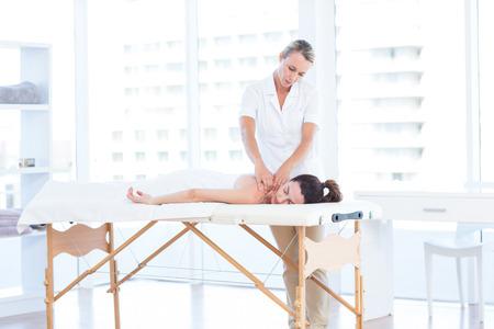 Mujer que tiene masaje de espalda en el consultorio médico